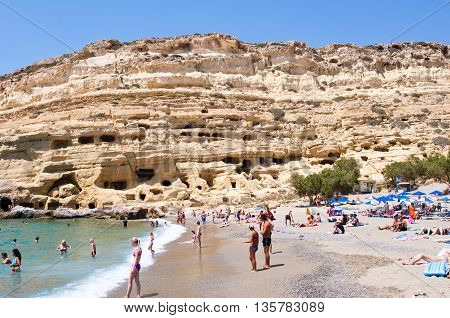 CRETE GREECE-JULY 22: Crowd of tourists on Matala beach with the caves on July 222014 Crete Greece.