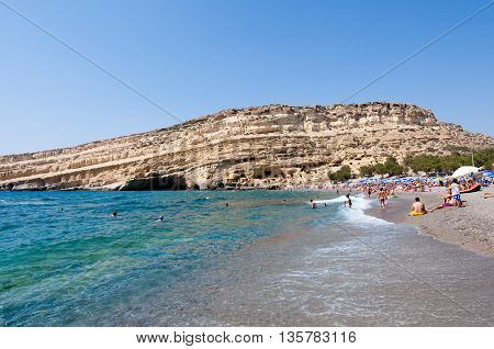CRETE GREECE-JULY 22: Tourists on Matala beach with the caves on July 222014 Crete island Greece.
