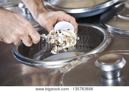Hands Filling Butterscotch Ice Cream With Spatula In Cup