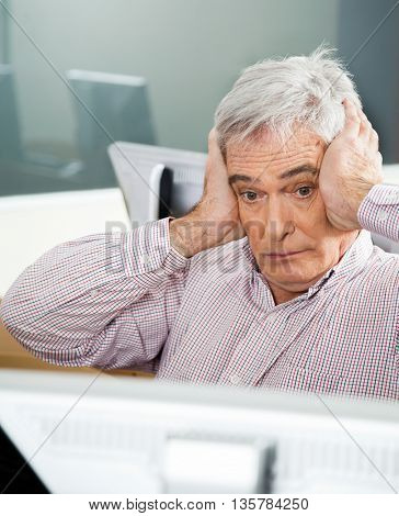 Shocked Senior Man Looking At Computer In Classroom