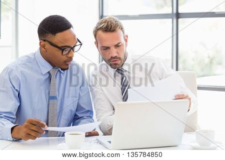 Businessmen sitting and discussing a report in office