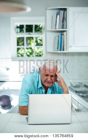 Worried senior man using laptop in kitchen at home