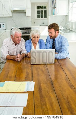 Agent talking to senior couple while sitting at table