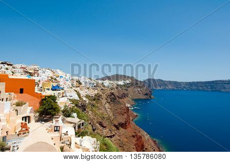 Oia architecture with whitewashed buildings carved into the rock on the edge of the caldera cliff on the island of Thira (Santorini) Greece.