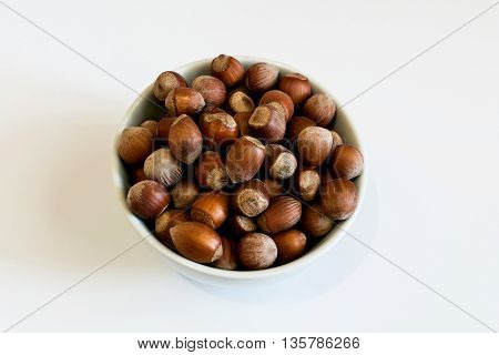Hazelnuts in a round bowl on a white background