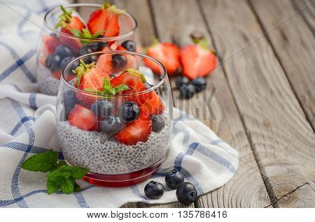 Chia seed pudding with strawberries and blueberries, selective focus, copy space