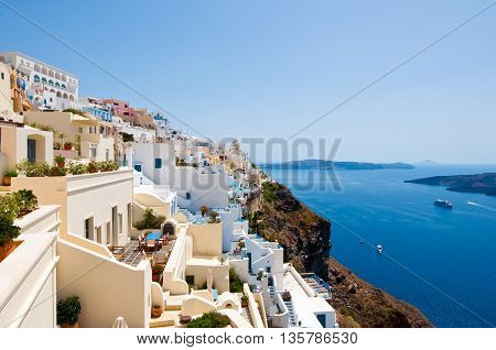 Panorama of Fira with whitewashed buildings carved into the rock on the edge of the caldera cliff on the island of Thira (Santorini) Greece.