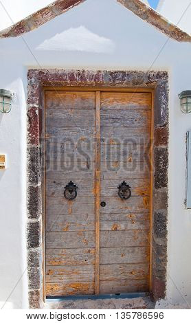 Wooden door from whitewashed house carved into the rock in Fira town on the island of Thira (Santorini) Greece.