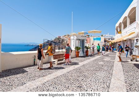 SANTORINI FIRA-JULY 28: Tourists enjoy view on July 28 2014 in Fira town on the Santorini island Greece. Fira is the modern capital of the Greek Aegean island Santorini.