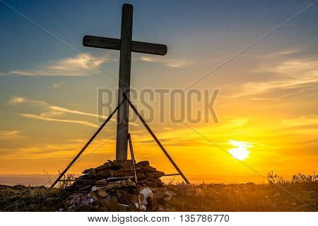 Christian wooden cross on the hill at sunset