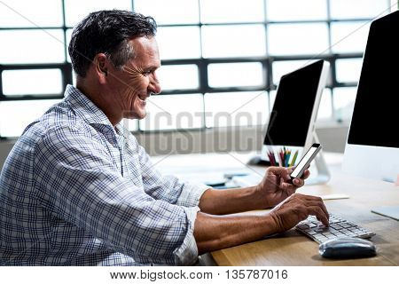 Man text messaging on mobile phone while using computer in office