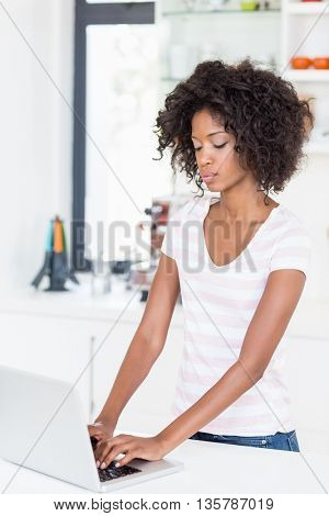 Young woman using laptop on kitchen worktop