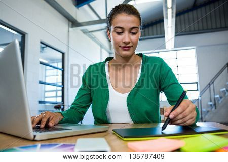 Graphic designer drawing on a graphic tablet while using laptop in office