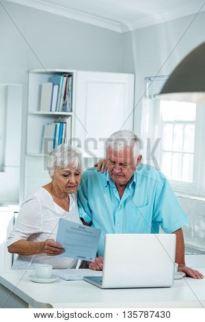 Senior man and woman reading document at home