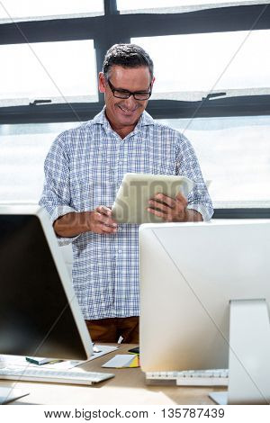 Happy man using digital tablet in office