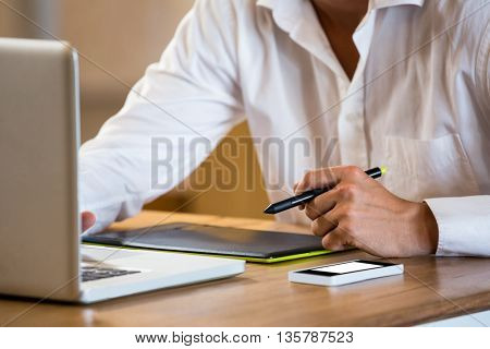 Mid section of man working on his graphics tablet in office