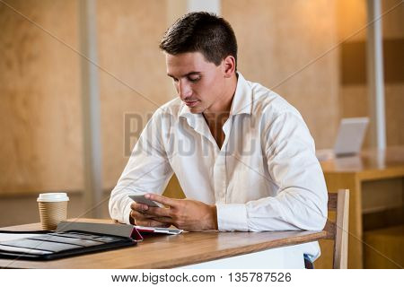 Man text messaging on mobile phone in office