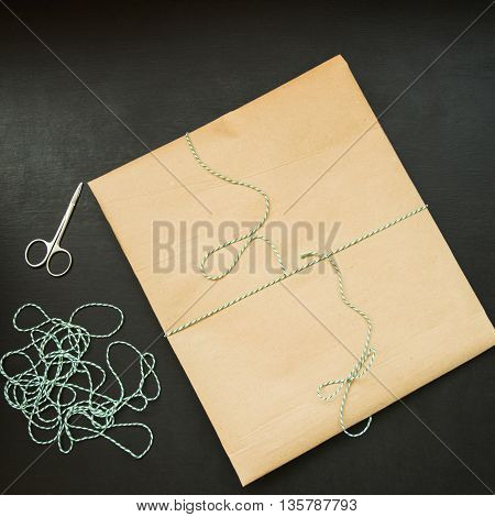 gift packing in kraft paper and tied green thread