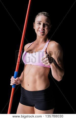 Female athlete holding a javelin and showing a thumbs up on black background