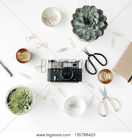feminini desk workspace with succulent retro camera scissors diary and golden clips on white background. flat lay top view