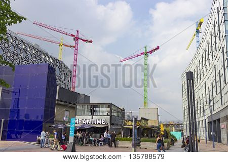 London England - May 27 2016: A series of vibrant and colourful cranes are used on this construction site to animate the Greenwich Peninsula Skyline alongside the River Thames in London England.