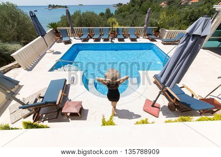 Young fashionable woman enjoying her vacation in villa beside the pool.Summer vacation,seaside villa house.Luxury lifestyle,successful woman on earned cruise.Europe summer holiday.Croatian island