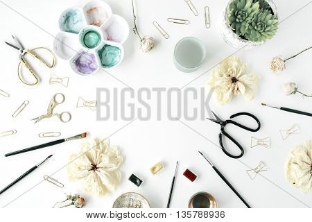 flat lay empty frame with bow tie clips scissors dry tulip roses palette succulent on white background. top view