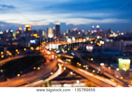 Abstract blurred light at twilights, overpass highway interchanged with city downtown background
