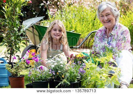 Portrait of grandmother and granddaughter gardening together in garden