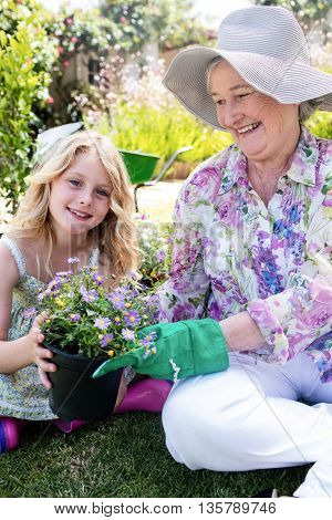 Grandmother and granddaughter holding a flower pot while gardening together