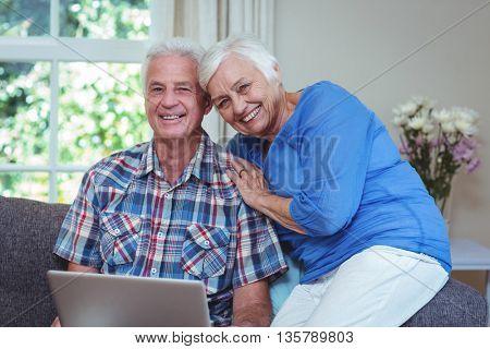 Portrait of happy senior couple using laptop at home