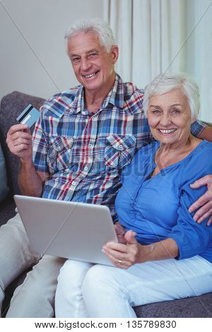 Portrait of smiling senior couple with credit card and laptop at home