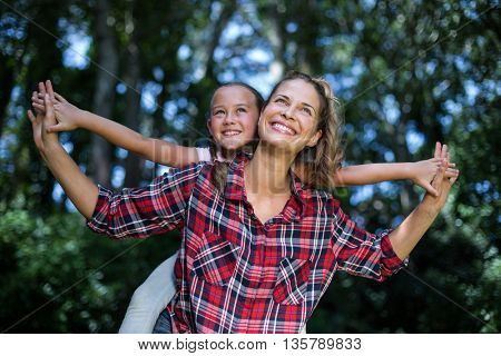 Playful mother and daughter looking up in back yard