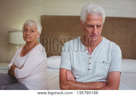 Unhappy senior couple after arguing while sitting on bed at home