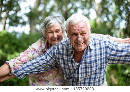 Happy senior couple with arms outstretched while standing in back yard