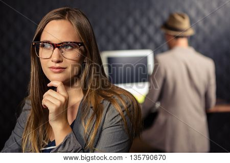 Thoughtful creative businesswoman holding her chin in office