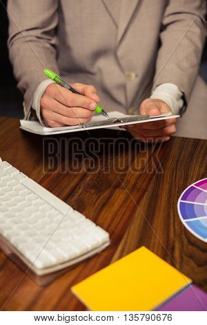 Creative businessman writing on a clipboard in office