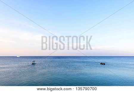 Photo of sea in protaras cyprus island with boats at sunset.
