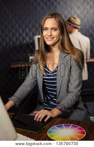 Creative businesswoman using computer and graphic tablet in office