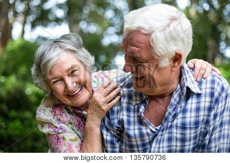 Senior couple enjoying against trees in back yard