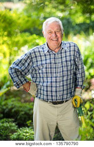 Portrait of happy senior man standing with equipment in garden