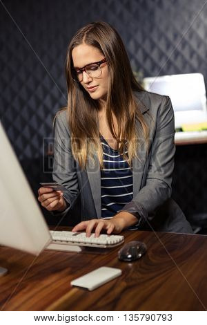 Creative businesswoman using her credit card in office