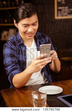 Hipster man using smartphone while drinking coffee in a coffee shop