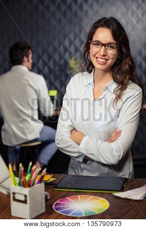 Creative businesswoman with arms folded in office