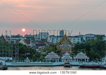 View from above on Wat Arun Temple of Dawn complex and wharf with sunset sky on the background. Urban Bangkok scene with Buddhist temple