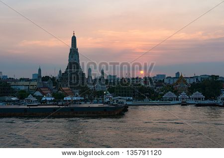 Aerial view of Wat Arun Temple of Dawn and wharf with sunset sky on the background. Urban Bangkok scene with Buddhist temple
