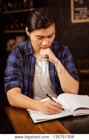 Hipster man writing on planner in coffee shop