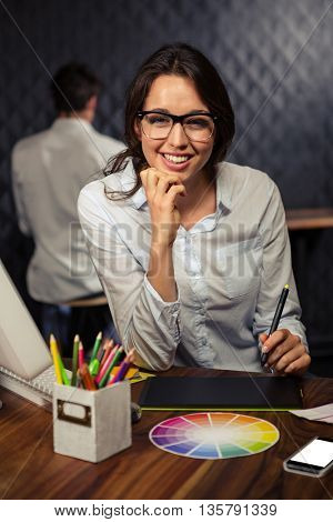 Creative businesswoman working on graphic tablet in office
