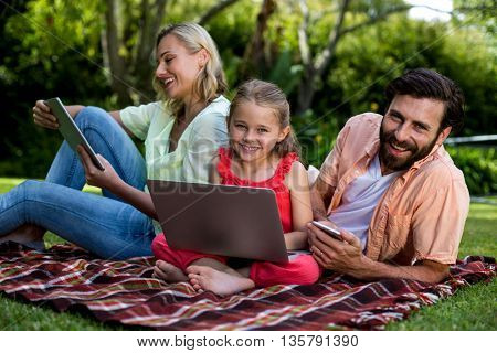 Happy family using technologies relaxing in yard