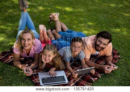 High angle view of smiling family using technologies while lying on grass in yard
